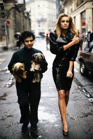 Fashion designer Azzedine Alaia holding his two Yorkshire terriers, Patapouf and Wabo, walking in Paris street with model Frederique who wears one of his creations, a black leather zippered dress, 1986. Courtesy of Arthur Elgort.